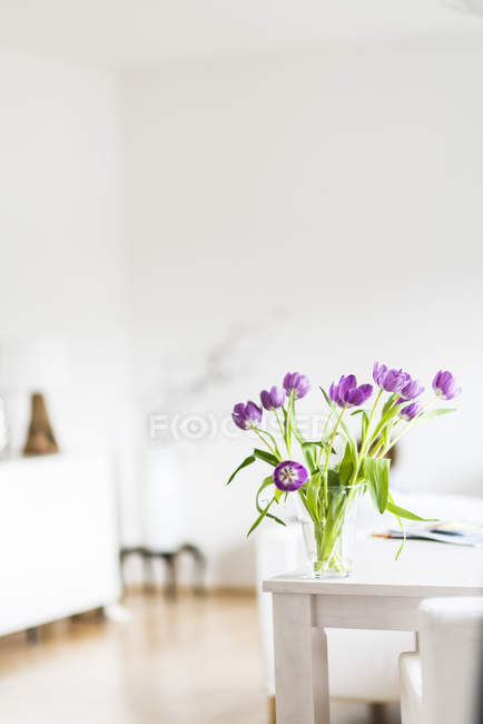 Fresh violet tulips in vase on table at home — Stock Photo