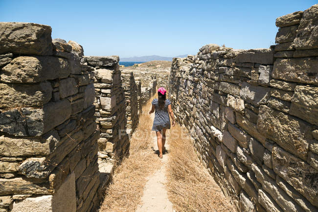 Delos, Mykonos, Greece.  Woman walking along the old houses in The island of Delos, one of the most important mythological, historical and archaeological sites in Greece. — Stock Photo