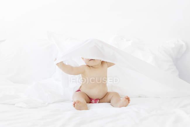 Menina sentada na cama branca e esconder o rosto sob folhas — Fotografia de Stock
