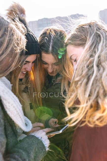 Quatro mulheres jovens se divertindo com smartphone — Fotografia de Stock