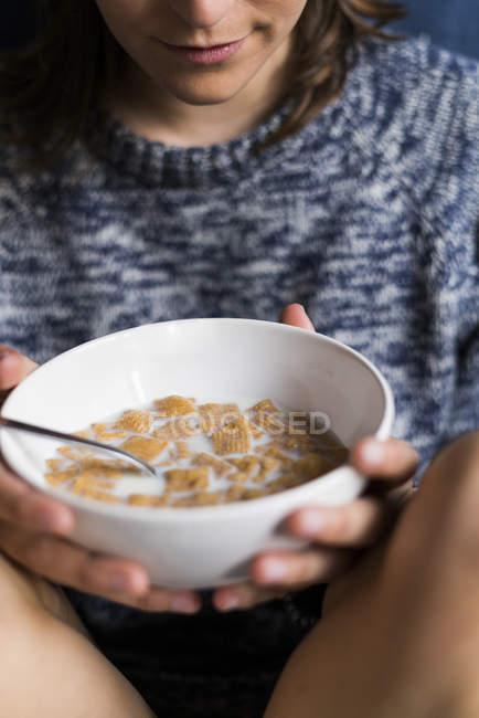 Молодая женщина ест овса с молоком на завтрак у себя дома — стоковое фото
