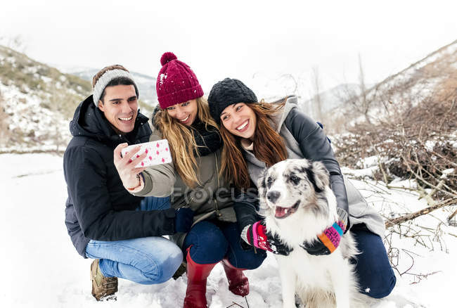 Leon, Spain, three friends making a selfie with their dog in the snow — Stock Photo