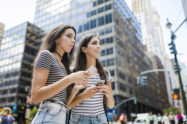 Sœurs jumelles marchant avec des téléphones cellulaires — Photo de stock