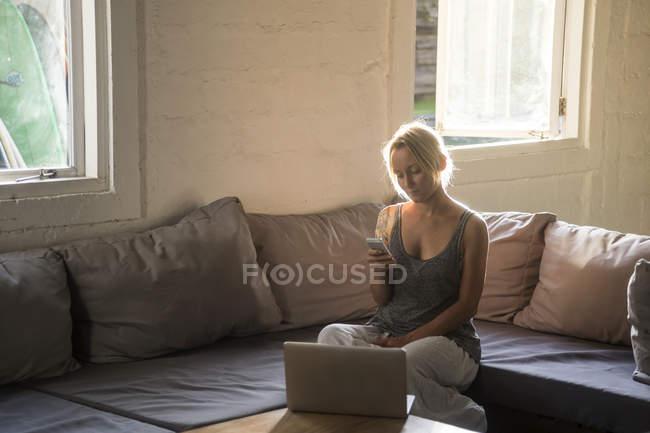 Donna bionda seduta sul divano e utilizzando il telefono cellulare — Foto stock