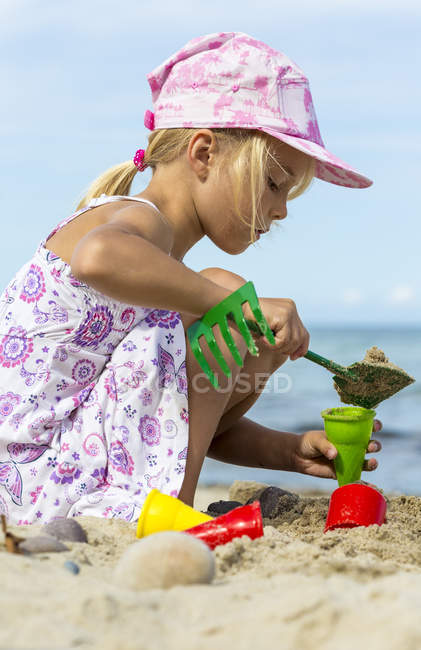 Little girl playing on the beach with sand — Stock Photo
