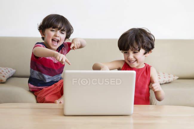 Hermanos viendo la película con ordenador portátil - foto de stock