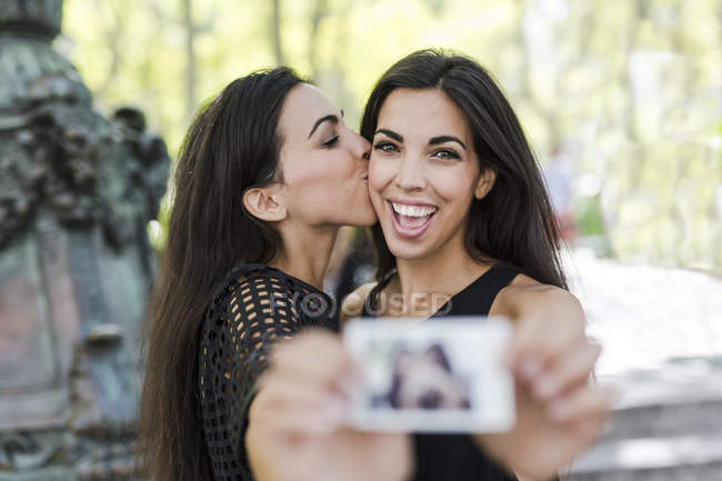 Twin sisters holding instant photo — стоковое фото