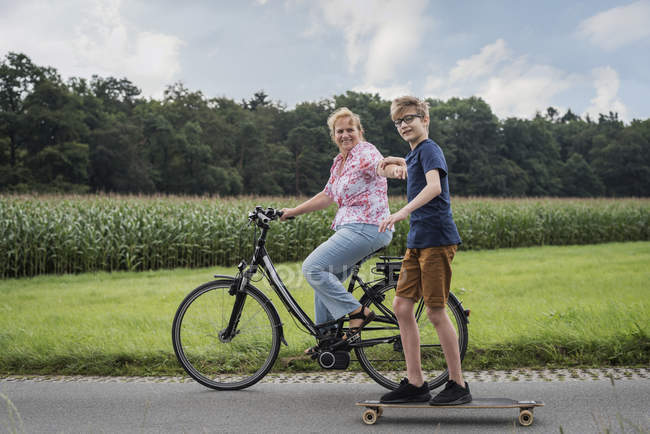 Grandson and grandmother riding bicycle and skateboard together — Stock Photo