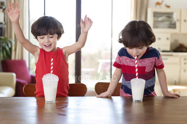 Boys playing with glasses of milk — Stock Photo