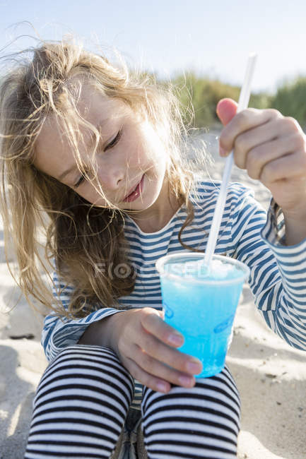 Girl stirring blue frozen drink with a straw on beach — Stock Photo