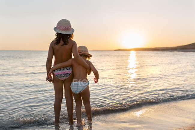 Вид сзади две сестренки, наблюдая закат на пляже Son Bou Бич, Балеарские острова, Испания — стоковое фото