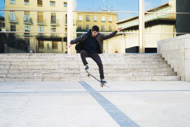 Skater boy jumping on skateboard, cityscape view on background — Stock Photo