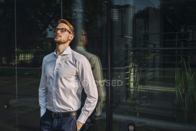 Портрет бизнесмена, стоящего у стены здания — стоковое фото