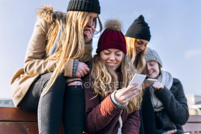 Four young women sharing smartphones on bench — Stock Photo