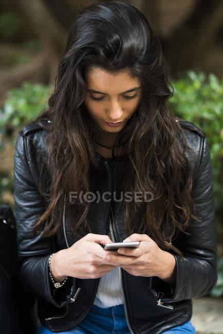 Mujer joven mensajes de texto en el teléfono - foto de stock