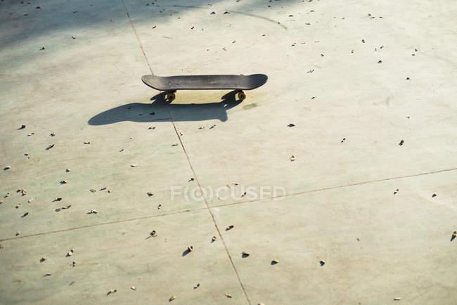 Skate no chão à luz do sol diurno — Fotografia de Stock