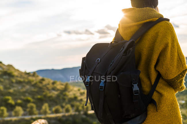 Woman standing with backpack in nature — Stock Photo