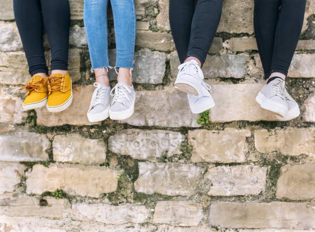 Gambe di quattro giovani donne davanti al muro di mattoni — Foto stock