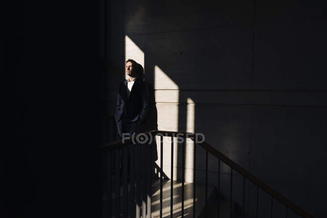 Portrait of businessman standing in shadows near wall — Stock Photo