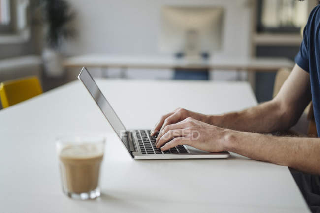 Cropped view of man using laptop at table — Stock Photo