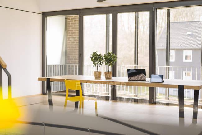 Vista di giorno del tavolo da ufficio con computer portatile e piante in vaso — Foto stock