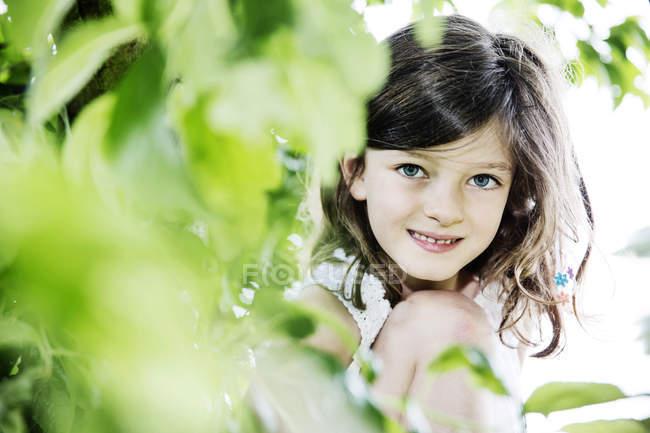 Menina agachado atrás da árvore, olhando para a câmera — Fotografia de Stock