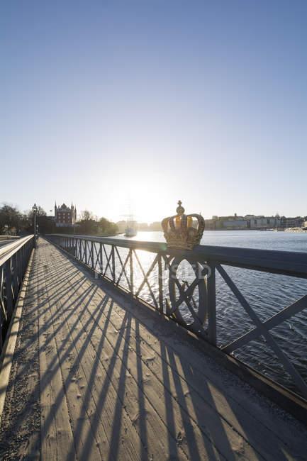 Швеція, Стокгольм, Шведська королівська Корона на перила моста Skeppsholmen в підсвічування — стокове фото