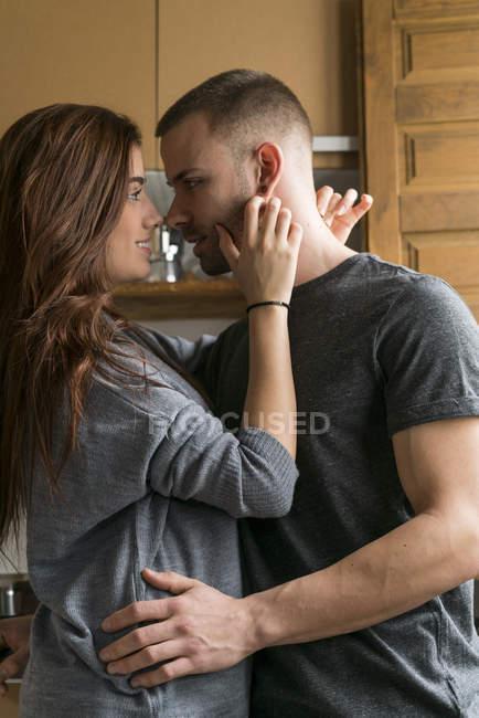 Casal de abraços em pé junto à cozinha — Fotografia de Stock