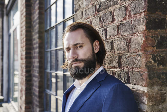 Businessman standing in front of brick building — Stock Photo