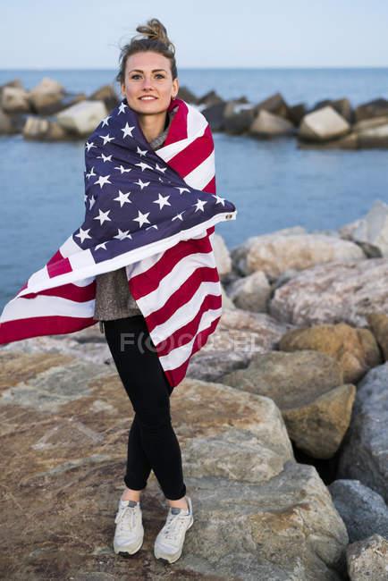 Ragazza avvolta nella bandiera americana in piedi vicino al mare — Foto stock
