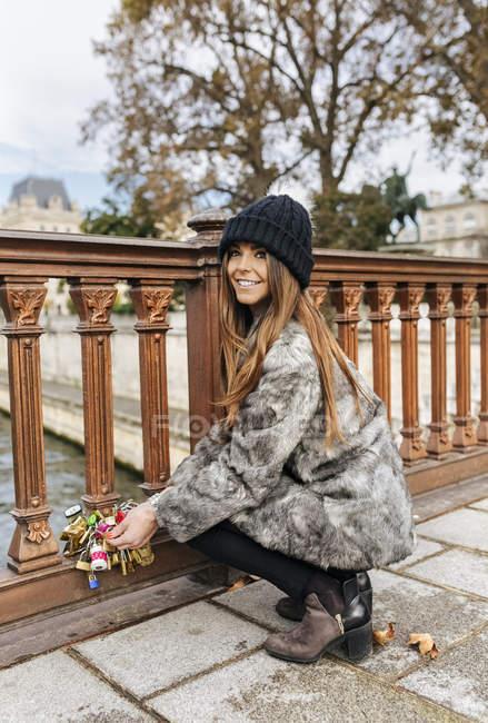 Parigi, Francia, bella donna mettere un lucchetto amanti su un ponte sulla Senna — Foto stock