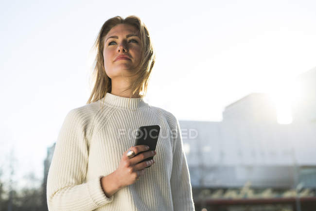 Girl with smartphone in sunny daylight — Stock Photo