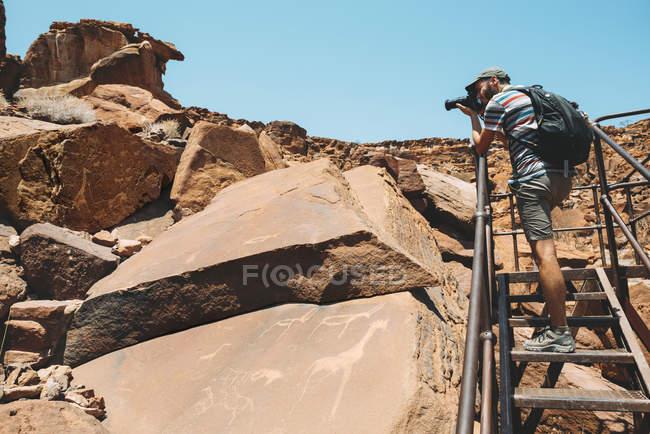Namibie, Damaraland, Twyfelfontein, homme prendre des photos de pétroglyphes — Photo de stock