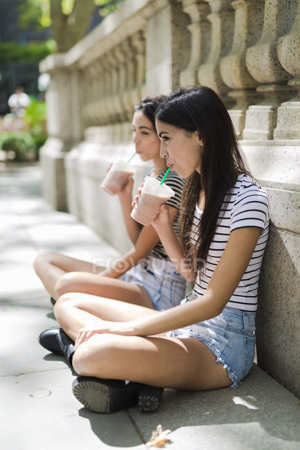 Twin sisters holding takeaway drinks — Stock Photo