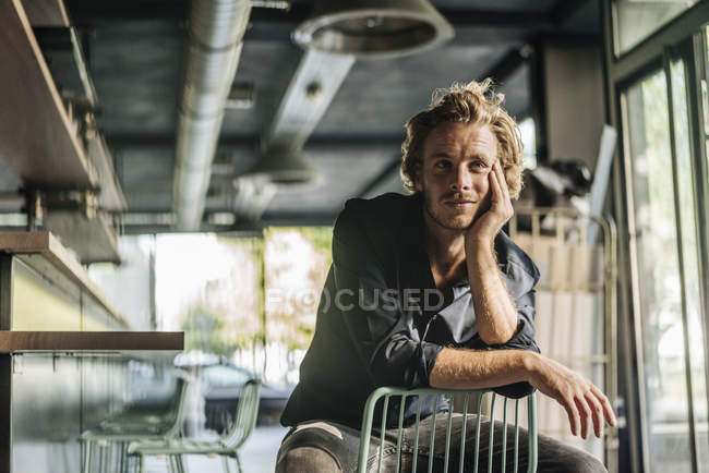 Blond man sitting on chair and thinking — Stock Photo