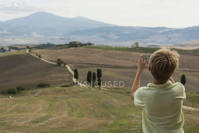 Italy, Tuscany, Boy taking picture of landscape — Stock Photo