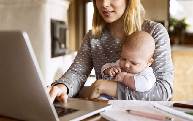 Madre con bambino utilizzando il computer portatile a casa — Foto stock
