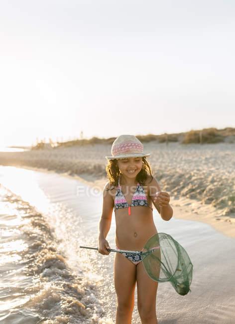 Маленькая девочка играет с рыболовной сетью на пляже, Son Bou пляж, Балеарские острова, Испания — стоковое фото