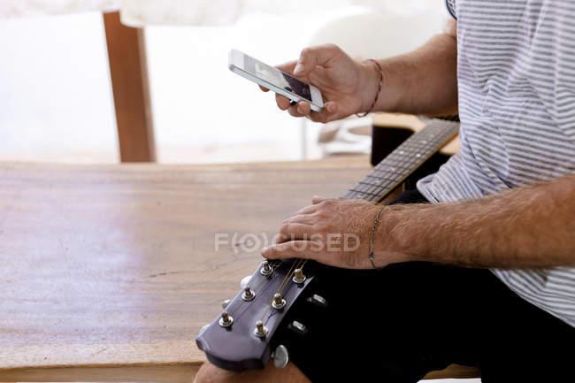 Close-up do homem segurando a guitarra e telefone celular — Fotografia de Stock