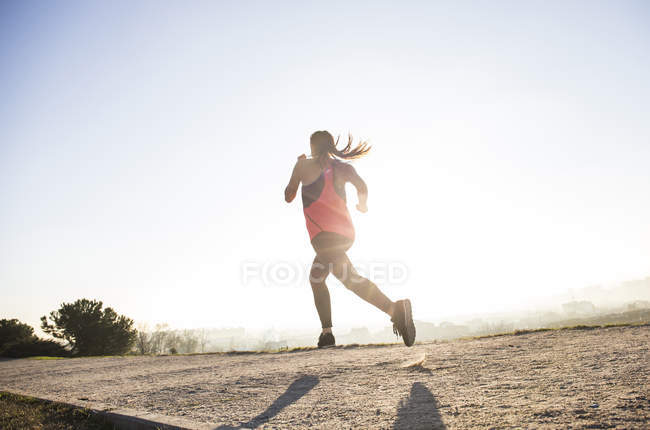 Молода жінка працює на шлях у sunlight — стокове фото