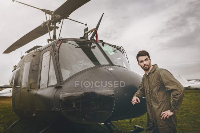 Man in overall standing next to a helicopter and looking sideways — Stock Photo