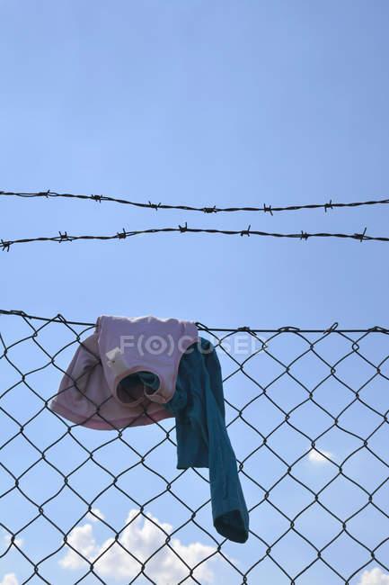 Crianças roupas penduradas na cerca de malha de arame — Fotografia de Stock