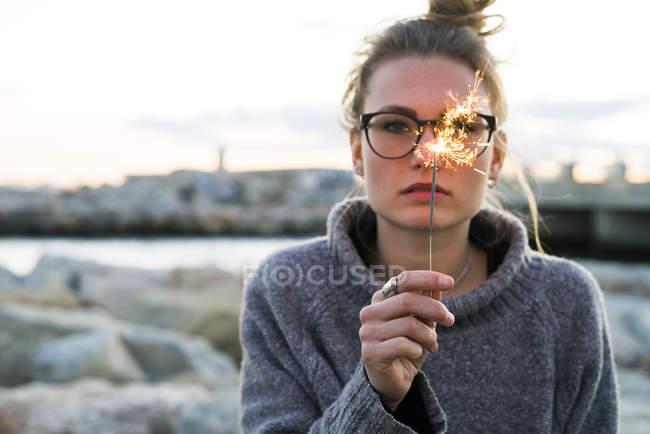 Girl in glasses with hair bun holding burning sparkler — Stock Photo