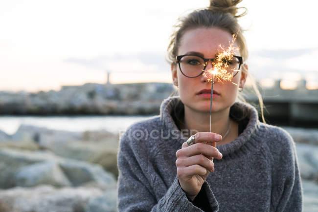 Girl in glasses with hair bun holding burning sparkler — Stock Photo