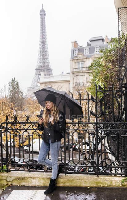 Париж, Франция, молодая женщина, используя свой смартфон под дождем с Эйфелевой башней на заднем плане . — стоковое фото