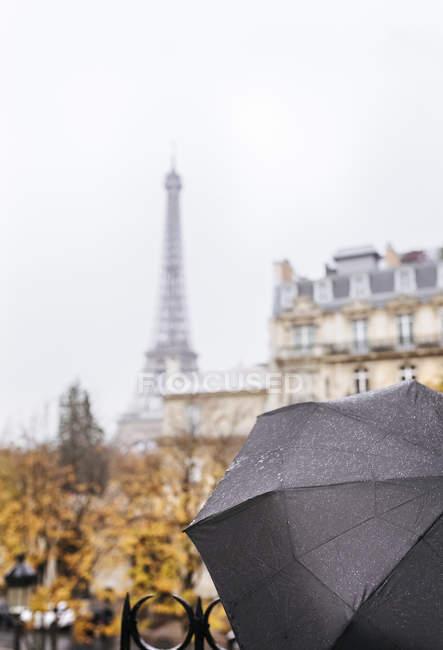 Paris, França, guarda-chuva preto sob a chuva com a Torre Eiffel no fundo . — Fotografia de Stock