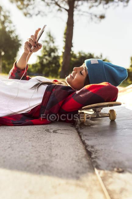 Gijn, Asturie, Spagna, skateboarder girl invia messaggi con il suo smartphone nello skatepark — Foto stock