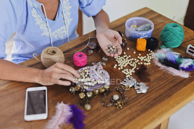 Woman doing handicraft at wooden table — Stock Photo
