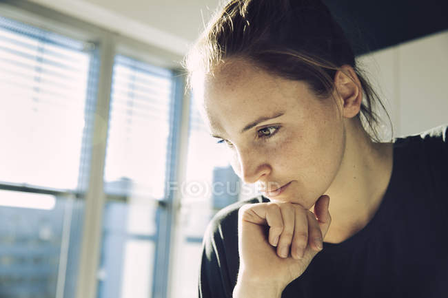 Pensive young woman holding hand on the chin — Stock Photo
