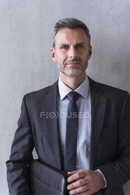 Businessman standing in front of grey wall — Stock Photo
